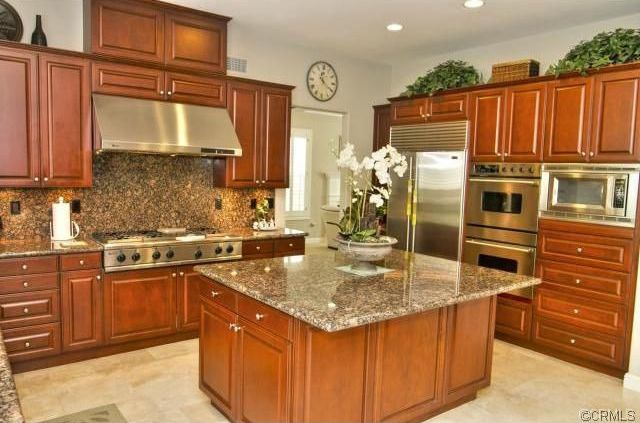 Traditional Kitchen with stone tile floors, full backsplash, Built In Refrigerator, Kitchen island, electric cooktop, Flush