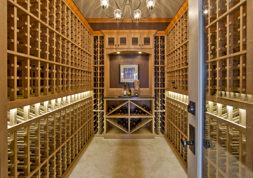 Traditional Wine Cellar with Chandelier, stone tile floors, Standard height, Built-in bookshelf, Crown molding, can lights