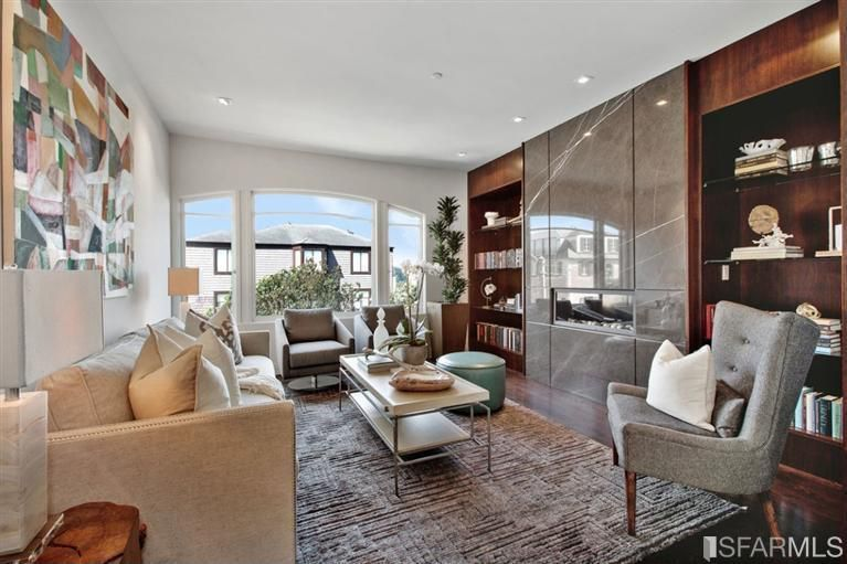 Contemporary Living Room with Arched window, can lights, Built-in bookshelf, Hardwood floors, Standard height