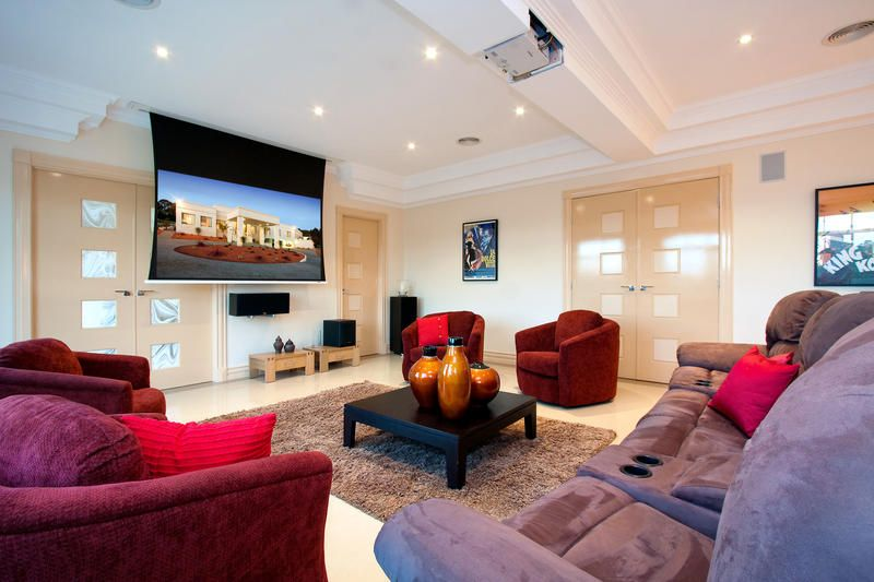 Modern Home Theater with Glass panel door, Exposed beam, Concrete floors, can lights, Standard height