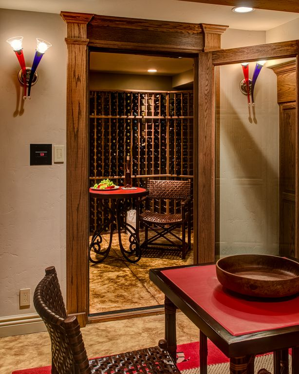 Craftsman Wine Cellar with Standard height, Concrete floors, Built-in bookshelf, Wall sconce, can lights, French doors