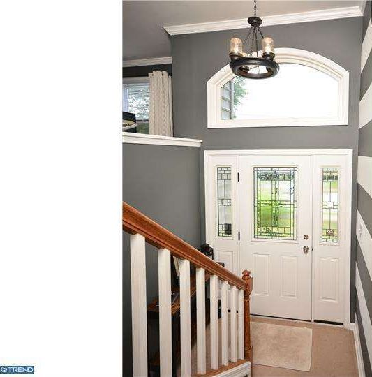 Traditional Entryway with Chandelier, Glass panel door, Carpet, Arched window, High ceiling, Paint 2, Paint 1, Crown molding