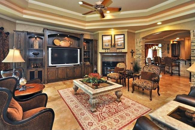 Traditional Living Room with Built-in bookshelf, stone tile floors, Standard height, Fireplace, Ceiling fan, Crown molding