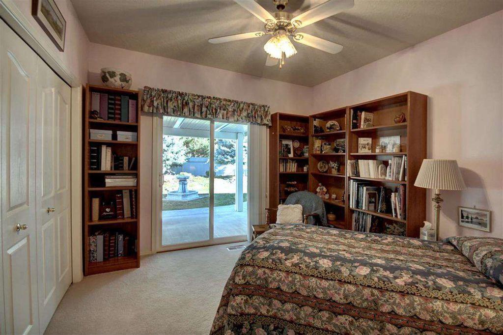 Traditional Guest Bedroom with Ceiling fan, Standard height, Built-in bookshelf, Hardwood floors, sliding glass door