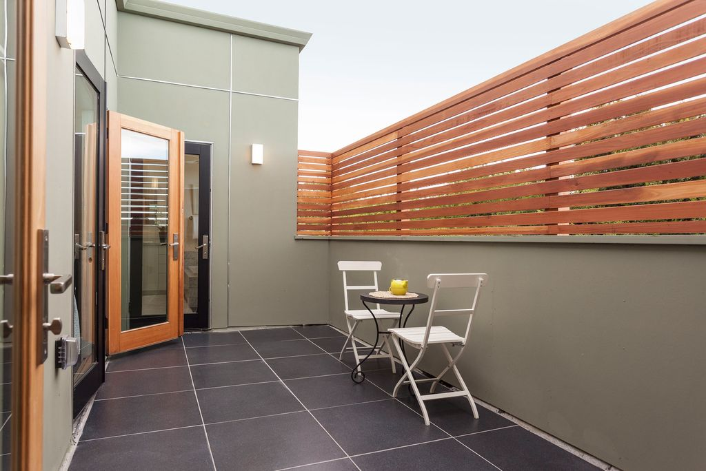 Contemporary Patio with exterior tile floors, French doors, Paint, Fence, Horizontal wood paneling