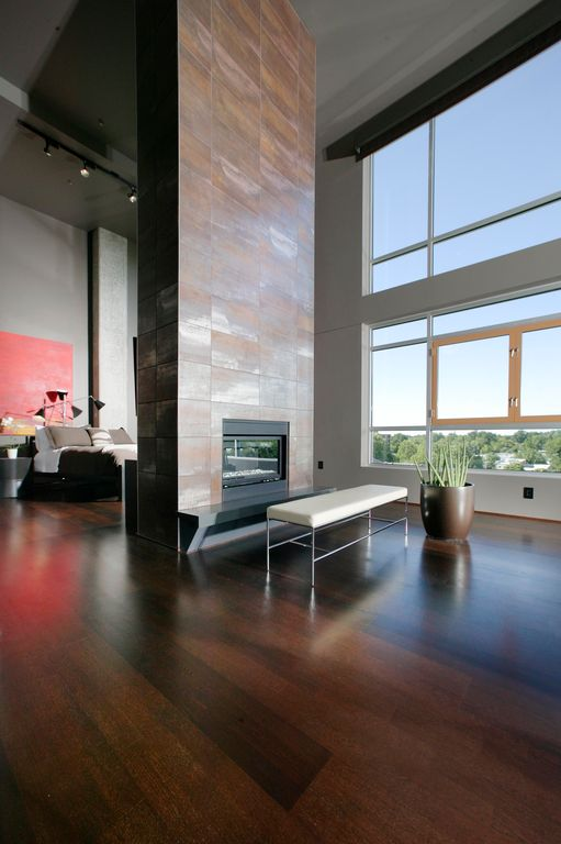 Modern Master Bedroom with metal fireplace, flush light, Laminate floors, Design Within Reach Grissini Bench, stone fireplace