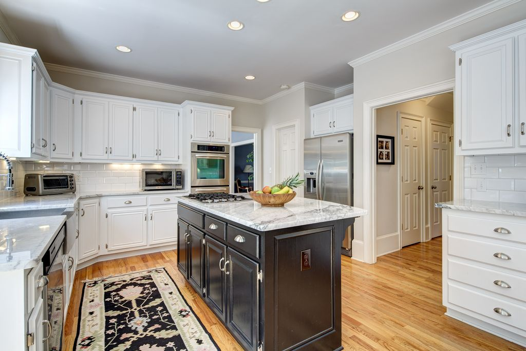 Traditional Kitchen with Farmhouse sink, Framed Partial Panel, Kitchen island, Hickory Hardware American Diner Cup Pull