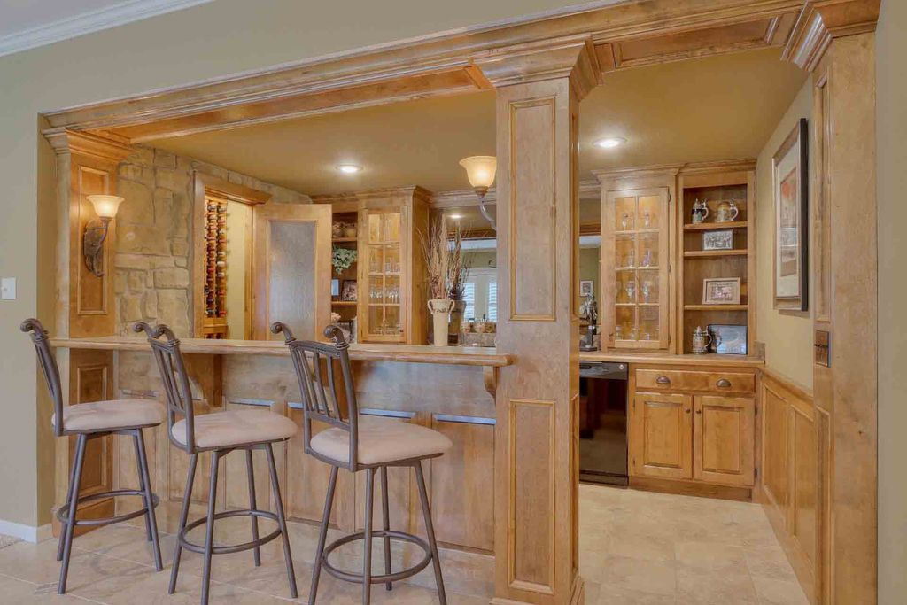 Country Bar with Columns, Crown molding, travertine tile floors, Raised panel alder cabinets, Wall sconce, Built-in bookshelf