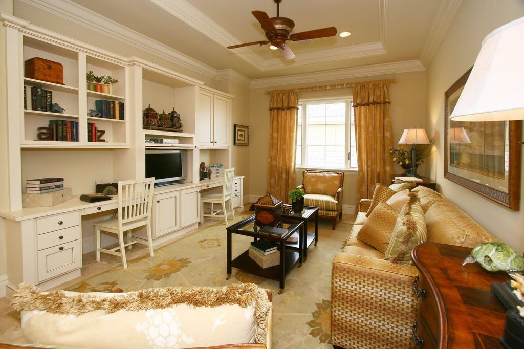 Traditional Home Office with Built-in bookshelf, Crown molding, can lights, sandstone floors, Ceiling fan, Casement