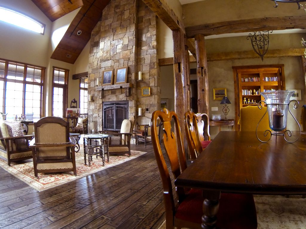 Traditional Living Room with High ceiling, picture window, can lights, stone fireplace, Casement, Hardwood floors, Fireplace