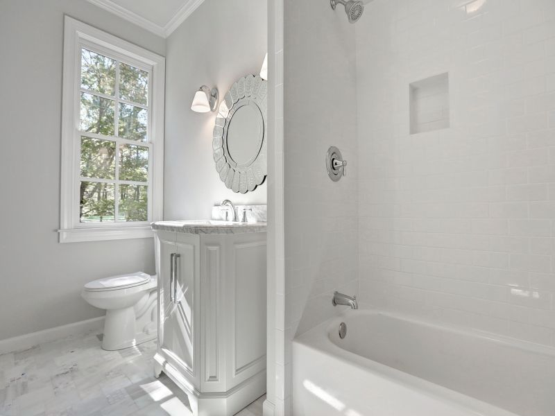 Traditional 3/4 Bathroom with partial backsplash, stone tile floors, Crown molding, Wall sconce, Undermount sink, Flush