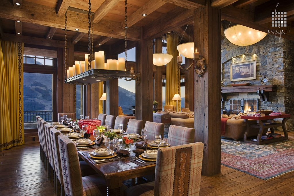 Rustic Dining Room with Hardwood floors, Chandelier, Floor to ceiling curtains, Columns, Wall sconce, can lights