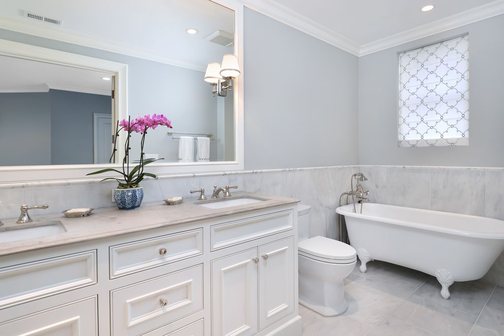 Traditional Master Bathroom with picture window, Crown molding, stone tile floors, Inset cabinets, Complex marble counters