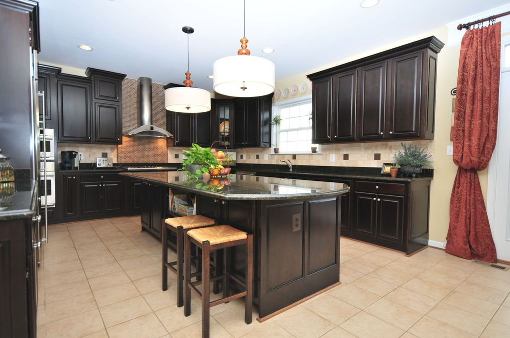 Traditional Kitchen with U-shaped, Inset cabinets, limestone tile floors, Breakfast bar, specialty door, Pendant light