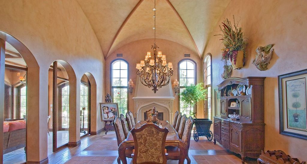 Mediterranean Dining Room with terracotta tile floors, Paint 1, Chandelier, can lights, Built-in bookshelf, Columns
