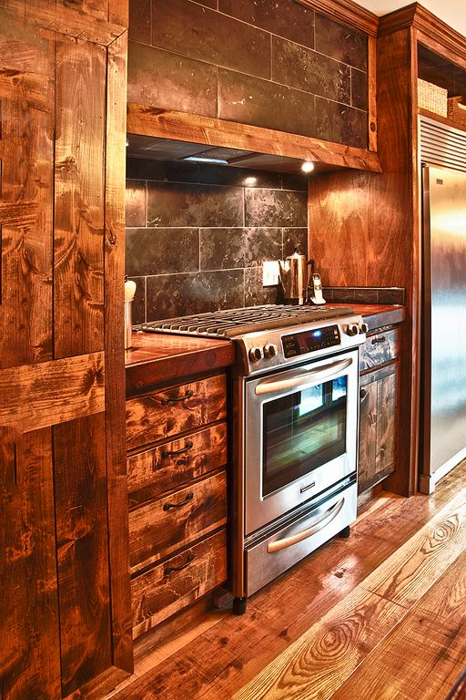 Rustic Kitchen with Framed Partial Panel, Reclaimed hardwood flooring, Built In Refrigerator, Wood counters, Standard height