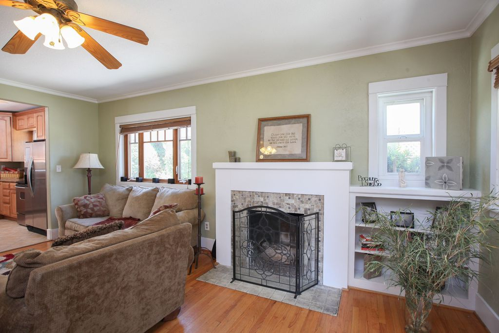 Traditional Living Room with Crown molding, Ceiling fan, Fireplace, Casement, Hardwood floors, metal fireplace