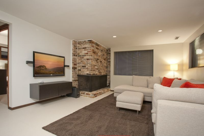 Contemporary Living Room with metal fireplace, Concrete floors, Standard height, brick fireplace, can lights, Fireplace
