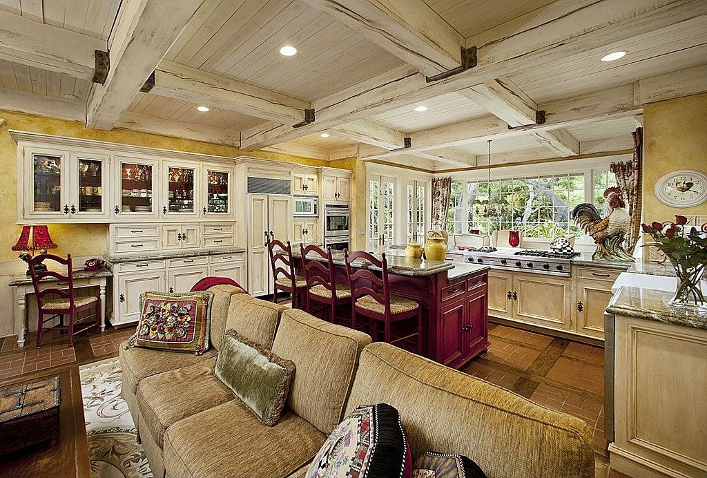 Country Great Room with Wainscotting, Exposed beam, terracotta tile floors, can lights, High ceiling, Casement, French doors