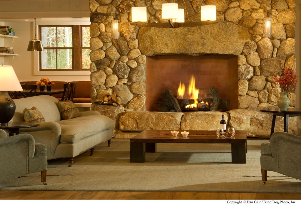 Rustic Living Room with Wall sconce, stone fireplace, Hardwood floors, Chandelier