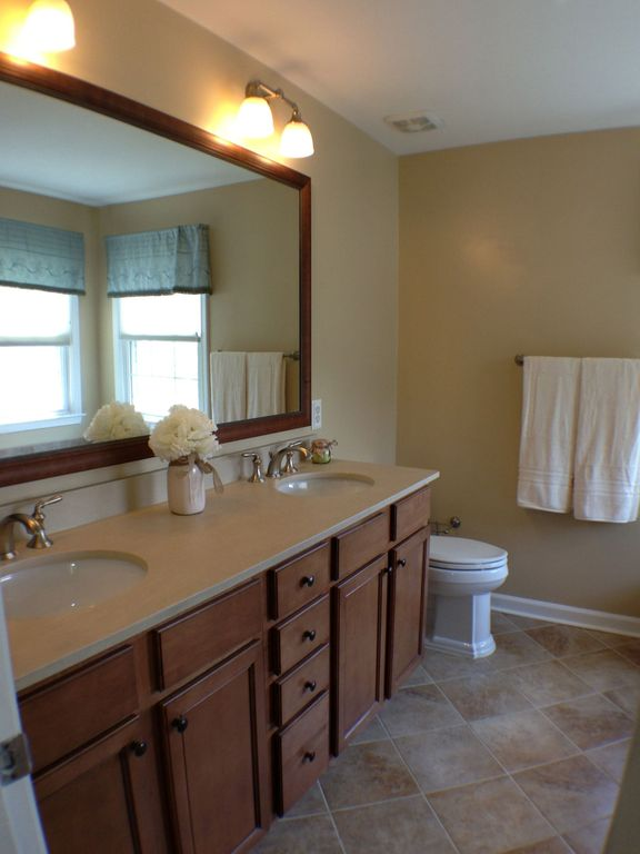 Traditional Master Bathroom with Double sink, Flat panel cabinets, Undermount sink, limestone tile floors, Limestone counters