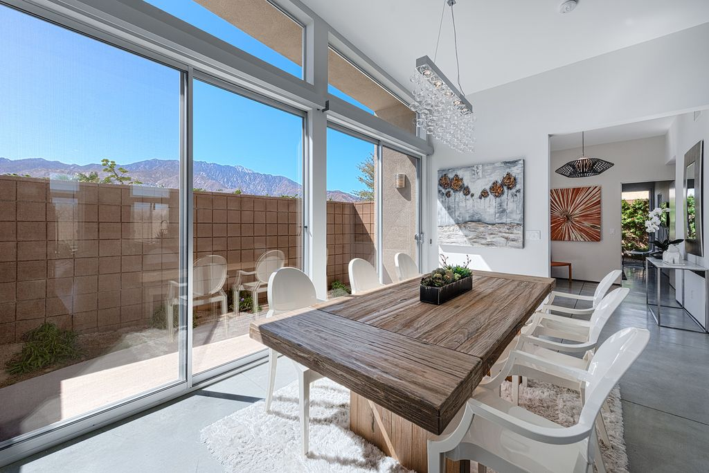 Contemporary Dining Room with can lights, Standard height, sliding glass door, Concrete tile , Transom window, Chandelier