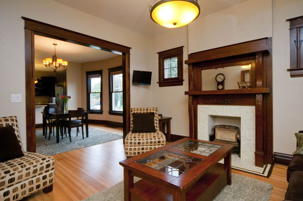 Craftsman Living Room with stone fireplace, picture window, Pendant light, Standard height, Fireplace, Hardwood floors