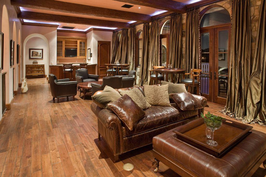 Mediterranean Living Room with six panel door, Arched window, Exposed beam, Hardwood floors, Crown molding, French doors