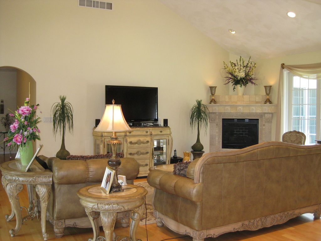 Traditional Living Room with Fireplace, can lights, stone fireplace, picture window, Laminate floors, metal fireplace