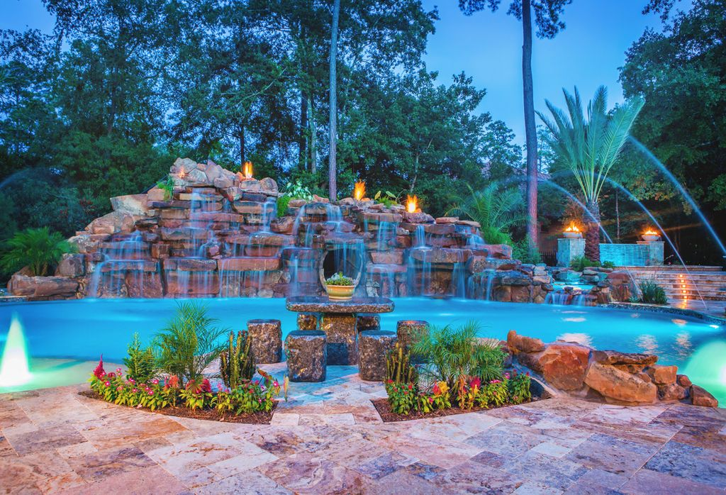 Rustic Swimming Pool with exterior stone floors, Other Pool Type, Exterior accent lighting, Waterfall, Fence, Fire pit