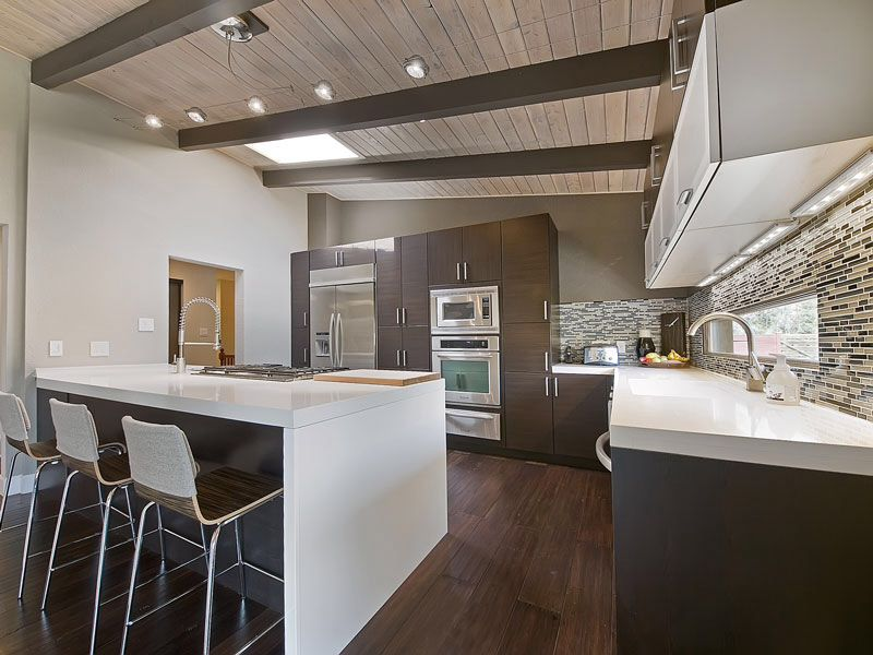 Contemporary Kitchen with full backsplash, European Cabinets, Built In Refrigerator, Skylight, wall oven, Standard height