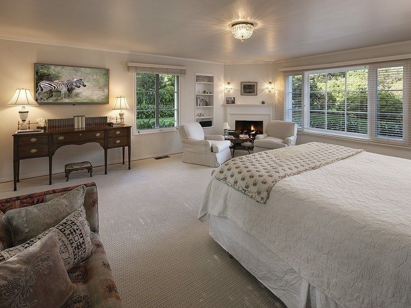 Traditional Master Bedroom with Wall sconce, Fireplace, flush light, Crown molding, Casement, Cement fireplace, Carpet