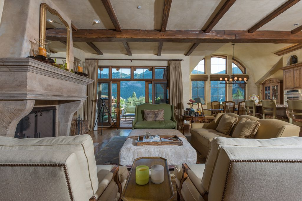 Mediterranean Great Room with French doors, Fireplace, Exposed beam, specialty window, Pendant light, Built-in bookshelf