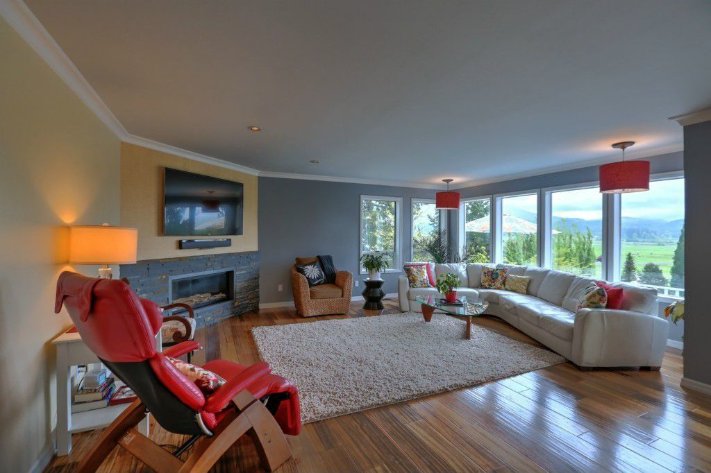 Contemporary Living Room with Hardwood floors, Standard height, can lights, Pendant light, picture window, Crown molding