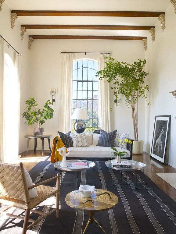 Mediterranean Living Room with Exposed beam, High ceiling, Hardwood floors, Arched window