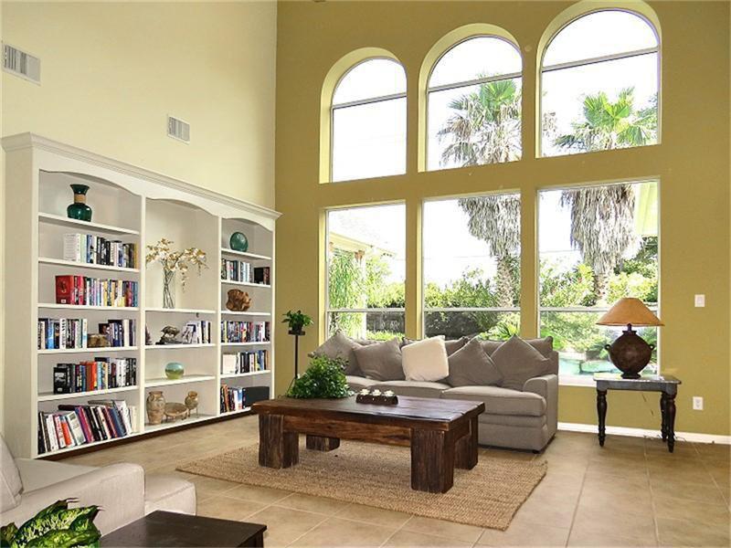 Mediterranean Living Room with Built-in bookshelf, High ceiling, stone tile floors, sandstone tile floors, Arched window