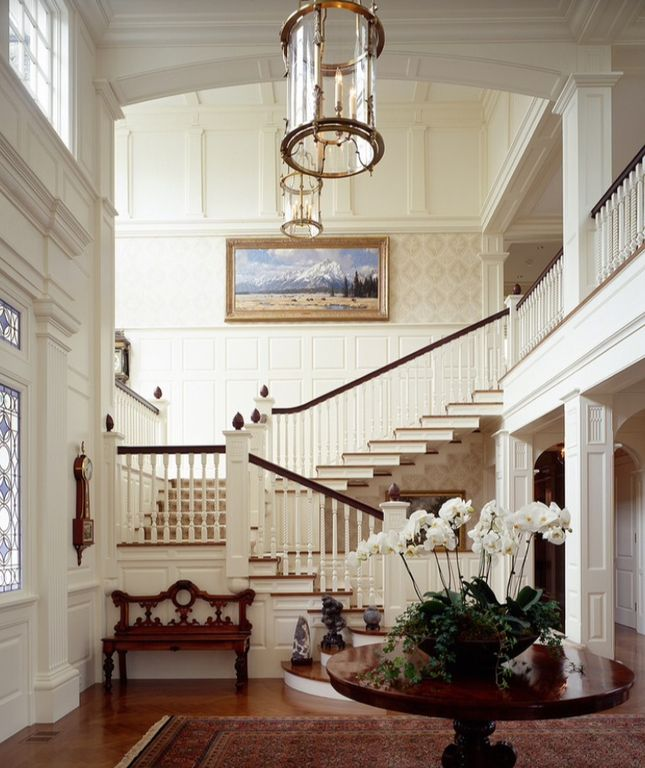 Traditional staircase with interior wallpaper columns chandelier