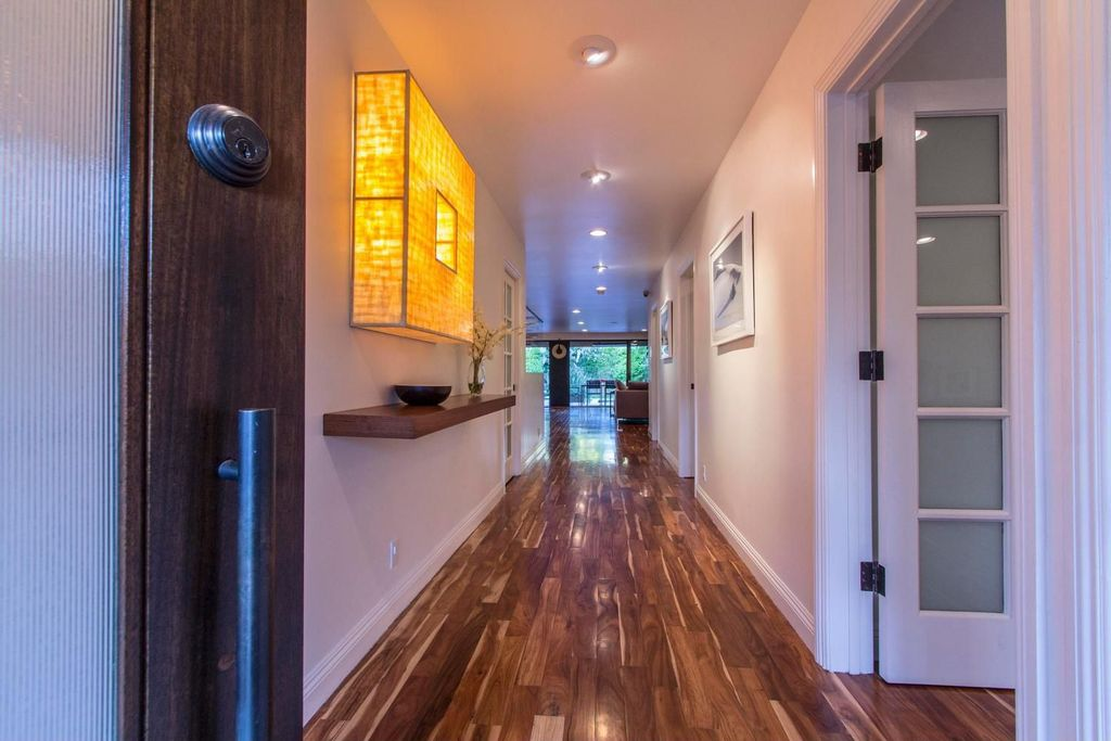 Contemporary Hallway with Zebrawood flooring, Built-in bookshelf, Yellow mosaic wall mounted light fixture, Paint, can lights