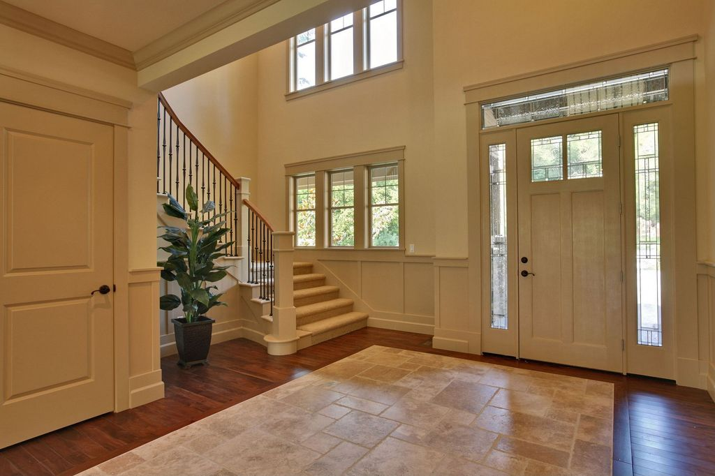 Traditional Entryway with stone tile floors, Crown molding, double-hung window, Laminate floors, flat door, Wainscotting