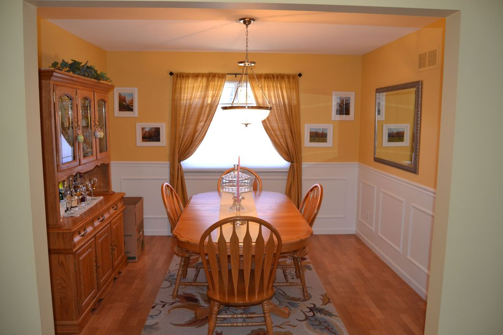 Traditional Dining Room with Casement, Pendant light, Standard height, Hardwood floors, Wainscotting