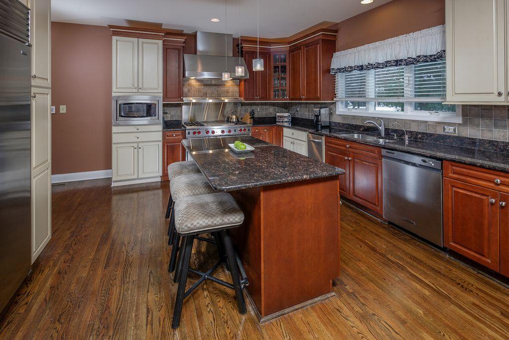 Traditional Kitchen with Paint 1, Raised panel, Pendant light, Multiple Sinks, full backsplash, specialty window, Wall Hood