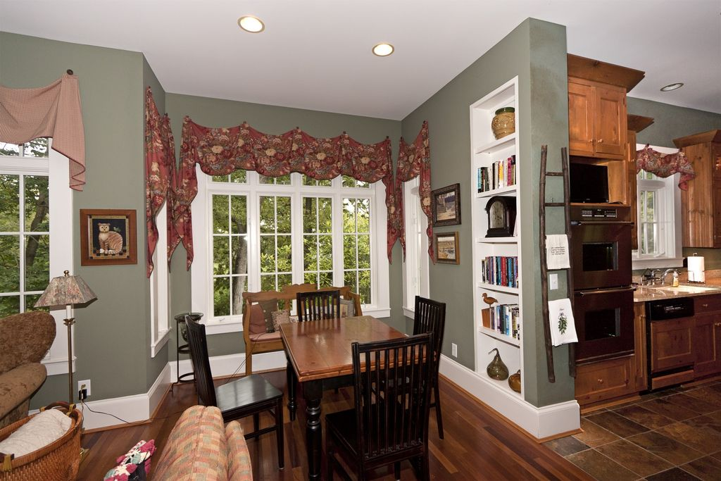 Country Dining Room with Casement, Hardwood floors, can lights, Standard height, Built-in bookshelf