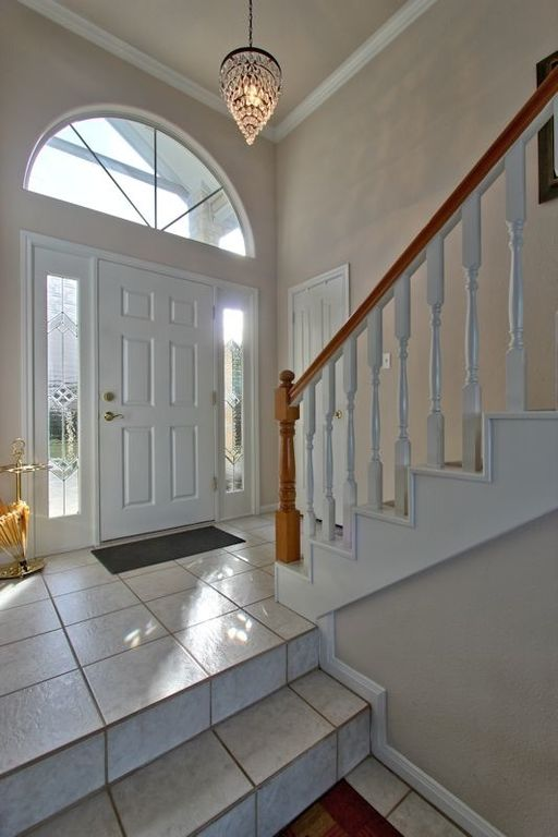 Traditional Entryway with Standard height, specialty door, Pendant light, limestone tile floors, Paint, Arched window