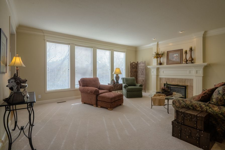 Traditional Living Room with Carpet, Fireplace, stone fireplace, picture window, Standard height, can lights, Crown molding