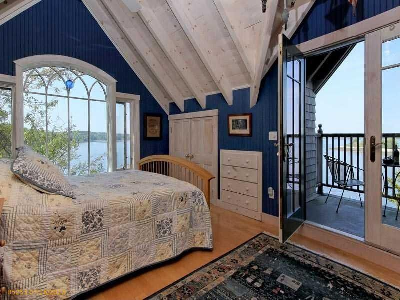 Cottage Guest Bedroom with interior wallpaper, specialty window, Laminate floors, French doors, Built-in bookshelf, Paint 1