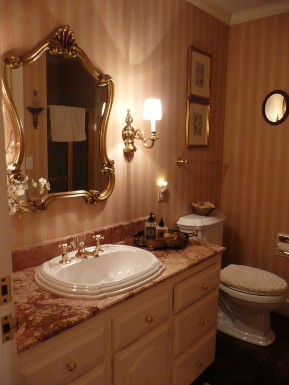 Traditional Powder Room with Raised panel, Burnt Gold Leaf Wall Sconce, Complex Marble, Concrete floors, Powder room