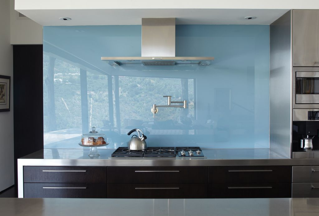 Contemporary Kitchen with Flat stainless steel countertops, can lights, Wall Hood, Standard height, Waterfall countertop