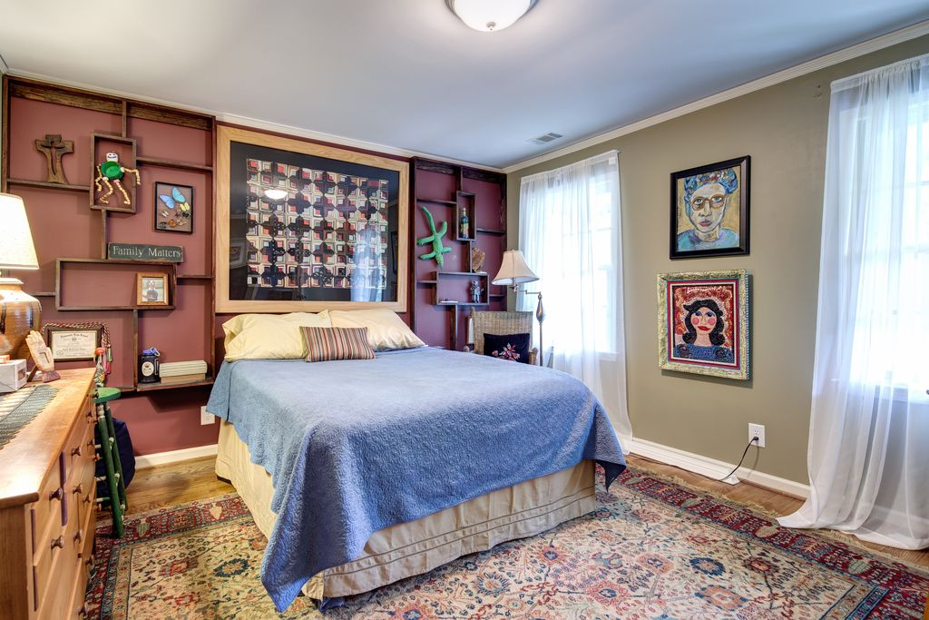 Eclectic Guest Bedroom with Hardwood floors, Built-in bookshelf, flush light, specialty window, Standard height