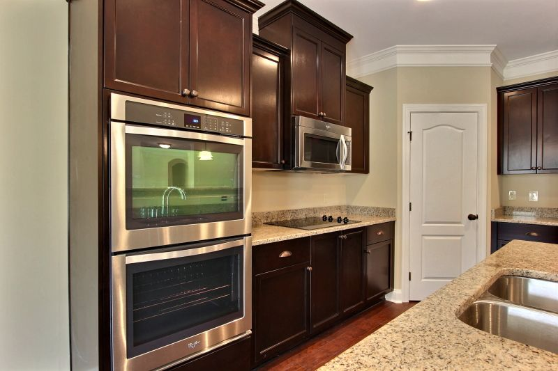 Traditional Kitchen with specialty door, electric cooktop, double wall oven, Kitchen island, Crown molding, Simple Granite