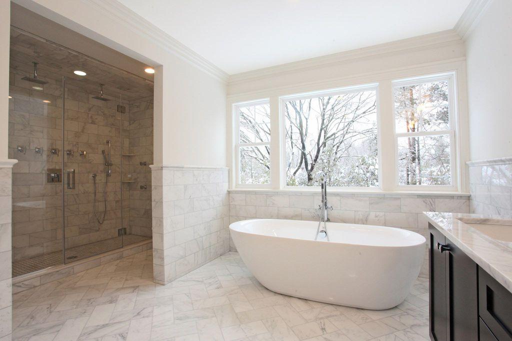 Traditional Master Bathroom with herringbone tile floors, Flat panel cabinets, Flush, stone tile floors, frameless showerdoor